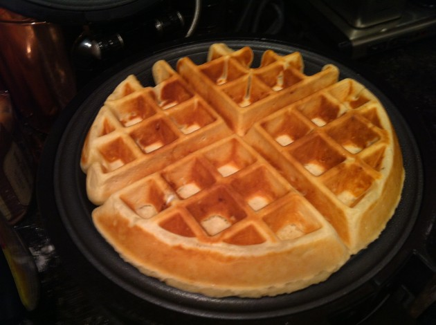 Hot, piping Belgian waffles coming out of the waffle maker